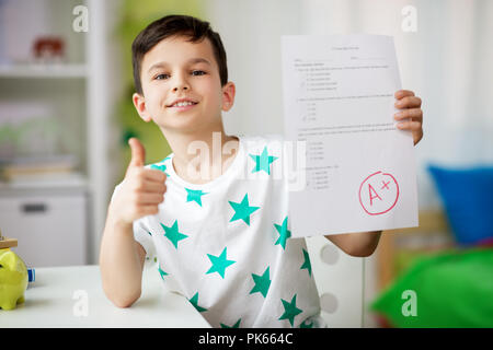 happy smiling boy holding school test with a grade - Stock Photo