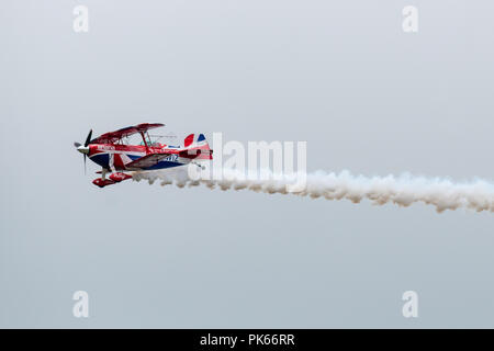 A rare moment of level flight for Rich Goodwin during his aerobatic display in his highly modified Pitts Special S2S Biplane. - Stock Photo