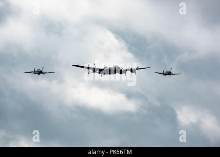 An Avro Lancaster PA474 of the Battle of Britain Memorial Flight  with accompanying Supermarine Spitfire and Hawker Hurricane - Stock Photo