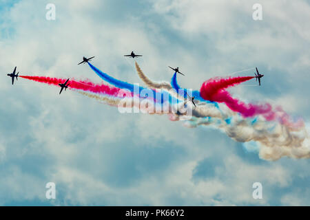 Seven of the nine Red Arrows Hawk jets perform the 'Vixen break' manoeuvre during an air display - Stock Photo