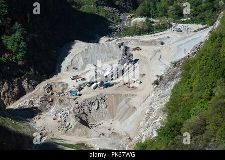 View of opencast mining quarry with  machinery at work - Stock Photo