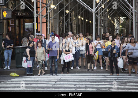 The crosswalks at 34th Street where 6th Avenue and Broadway cross are always busy with tourists, shoppers, and workers from the area in Manhattan, New York City. - Stock Photo