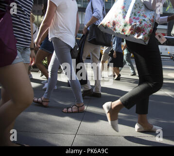 Pedestrians walking on East 42nd Street on a hot summer day in midtown Manhattan, New York City. - Stock Photo
