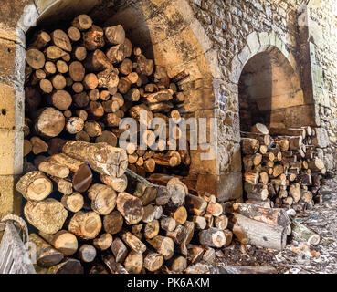 Piles of logs stored in medieval stone alcoves. - Stock Photo