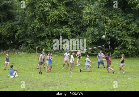 Group of young Latino Americans play volley ball in Prospect Park on the the July 4th holiday in Brooklyn, NY. - Stock Photo