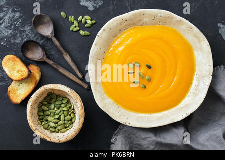 Pumpkin cream soup with toast and seeds on a rustic dark background. Top view, overhead, flat lay.