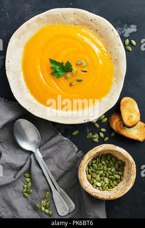 Pumpkin cream soup with toast on a concrete dark rustic background. Autumn winter warming soup. Flat lay