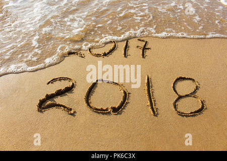 2017 and 2018 years written on sandy beach sea. Wave washes away 2017. - Stock Photo