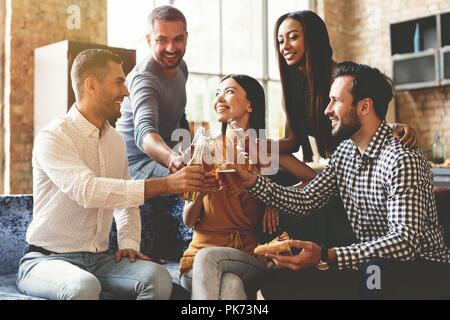 Spending great time with best friends. Group of cheerful young people enjoying food and drinks while spending nice time in cofortable chairs on the kitchen together. - Stock Photo