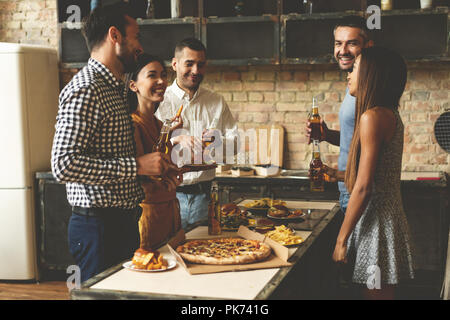 Home party. Full length of cheerful young people enjoying home party while communicating and eating snacks on the kitchen. - Stock Photo