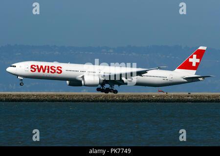 Boeing 777-3DE(ER) (HB-JNI) operated by Swiss landing at San Francisco International Airport (KSFO), San Francisco, California, United States of America - Stock Photo