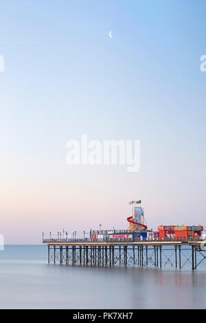 Moon rising over Paignton Pier in Torbay as the colours of sunrise burst across the sky and the ocean is calm. - Stock Photo