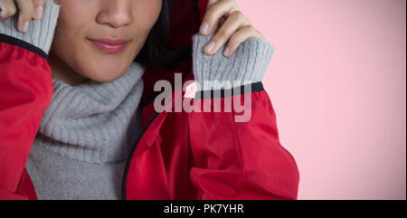 Composite image of smiling woman in hooded jacket standing against white background - Stock Photo