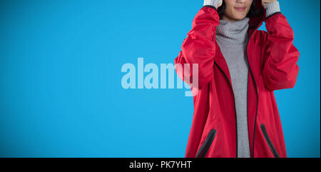 Composite image of woman in hooded jacket standing against white background - Stock Photo