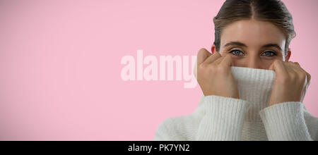 Composite image of portrait of young woman covering face with turtleneck sweater - Stock Photo