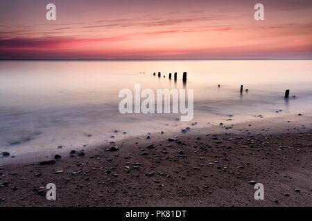 Dawn breaking over the beach groynes on Sandsend beach near Whitby on the North Yorkshire coast, England. - Stock Photo