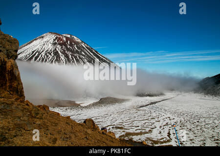 Devil's Staircase steep climbing to South Crater and view of Mt Ngauruhoe, Mt Doom, volcanic terrain partly covered by snow, Tongariro New Zealand - Stock Photo