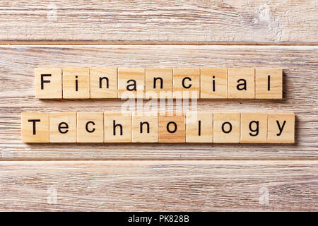 Financial Technology word written on wood block. Financial Technology text on table, concept. - Stock Photo