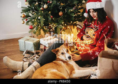 Happy Girl In Santa Hat Holding Phone And Hugging Dog Under Golden Beautiful Christmas Tree With