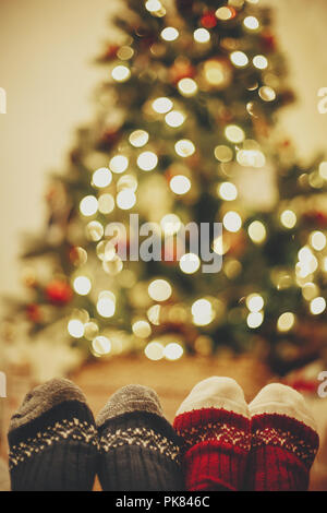 stylish festive socks on couple legs on background of golden beautiful christmas tree with lights in festive room. family relax time. cozy winter holi - Stock Photo