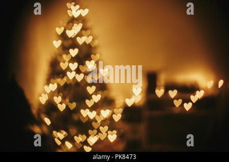 christmas abstract background, beautiful christmas tree golden lights hearts bokeh. blur of yellow glowing illumination in festive room. decor for win - Stock Photo