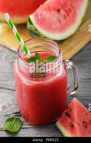 Smoothies cooked from a ripe watermelon in a transparent jar of fruit on a wooden table - Stock Photo