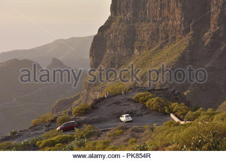 Mirador the Cherfe viewpoint, tourists enjoying evening view into Masca valley. High walls of Teno Massif in the northwest of Tenerife Canary Islands. - Stock Photo