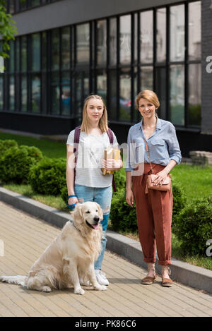 mother and teen daughter standing on street with their golden retriever - Stock Photo