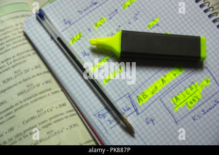 Close-up of a notebook and chemistry book of a young student while studying and doing homework - Stock Photo