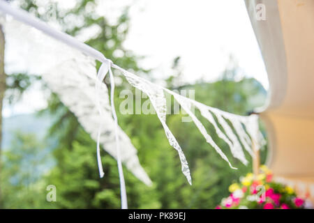 White Lace Wedding Banner Floating in the Wind Outside - Stock Photo