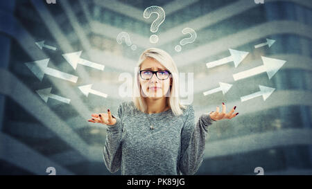 Confused young woman wearing glasses and frustrated hand gesture have to choose arrow direction, left or right side with interrogation marks above hea - Stock Photo