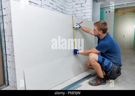 man measuring plasterboard sheet for interior construction - Stock Photo