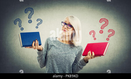Confused young student girl holding two different books has to choose between red and blue. Doubt and right choice concept. Left or right question whi - Stock Photo