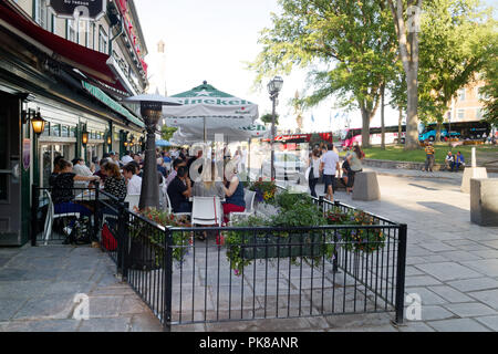 People eating on the busy tourist restaurant terrasses on Rue Ste Anne in Vieux Quebec, Canada - Stock Photo