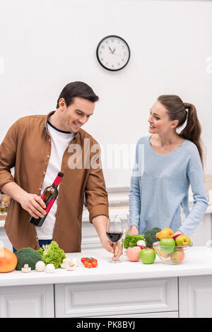 happy adult couple with red wine cooking together at kitchen - Stock Photo