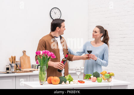 beautiful adult couple with red wine cooking together at kitchen - Stock Photo