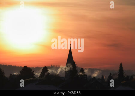Silhouette of a village with the church tower and houses with smoking chimneys, at sunrise, against a golden sky, on a winter morning, in Germany. - Stock Photo