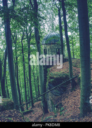Historical gazebo with reneval cupola roof stands on sandstone rock in the park. Around fresh green trees - Stock Photo
