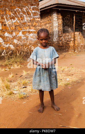 ALU - KINONDO, KENYA - MARCH 01, 2018: beautiful little Kenyan girl is standing in front of her house and looking at camera - Stock Photo