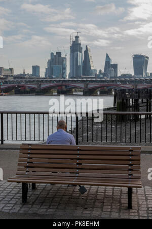 a man sitting on a wooden park bench on the south bank of the river thames in central London looking across the river towards the city of London. - Stock Photo