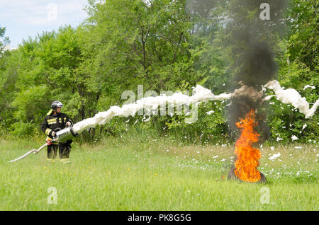 Komsomolsk-on-Amur, Russia - August 8, 2016. Public open Railroader's day. firefighter extinguish a burning tire during demonstration performances - Stock Photo