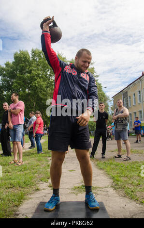 Komsomolsk-on-Amur, Russia - August 8, 2016. Public open Railroader's day. man raises weight in amateur competition - Stock Photo