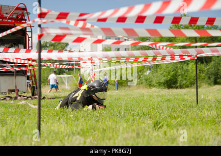 Komsomolsk-on-Amur, Russia - August 8, 2016. Public open Railroader's day. boy in the form of fireman crawl across the obstacle course - Stock Photo