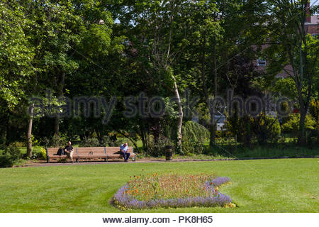 Lush green lawn with flower beds bordered by deciduous trees, Merrion Square, Dublin, Leinster, Ireland - Stock Photo