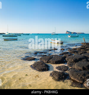 Boats in a sea at day time. Flat island on a background. Mauritius - Stock Photo