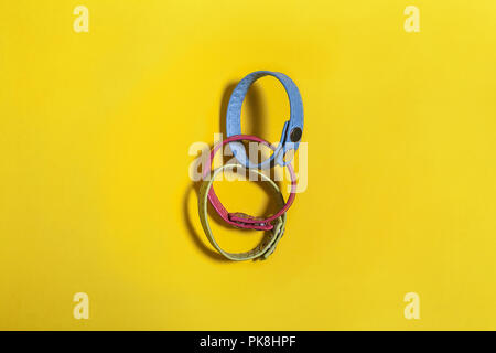set of three multicolored belt hand bracelets lying on a yellow background. free space for advertising text - Stock Photo