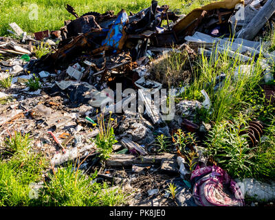 Illegal garbage dump. Large pile of metal, wooden and plastic waste. Pollution concept. - Stock Photo