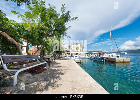Bench in the shade under trees in the port of Valun on the island Cres, Kvarner bay, Croatia - Stock Photo