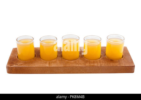 Yellow, same color opaque cocktails, a set of shots in one row, five servings on a wooden stand, substrate. Side view Isolated white background. Drink - Stock Photo