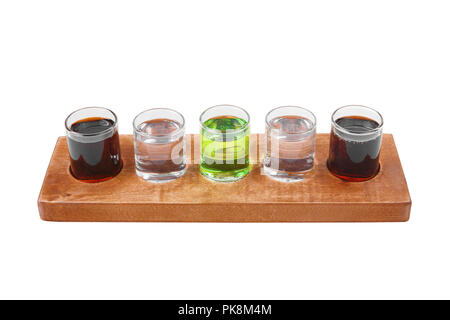 Multicolored transparent cocktails, a set of shots in one row, five servings on a wooden stand, substrate. Side view Isolated white background. Drink  - Stock Photo